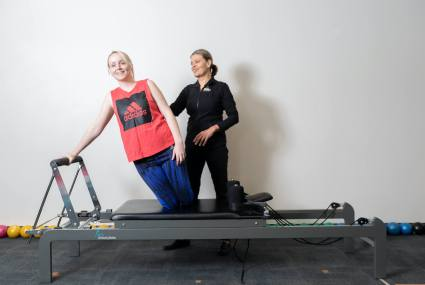 woman using clinical pilates reformer