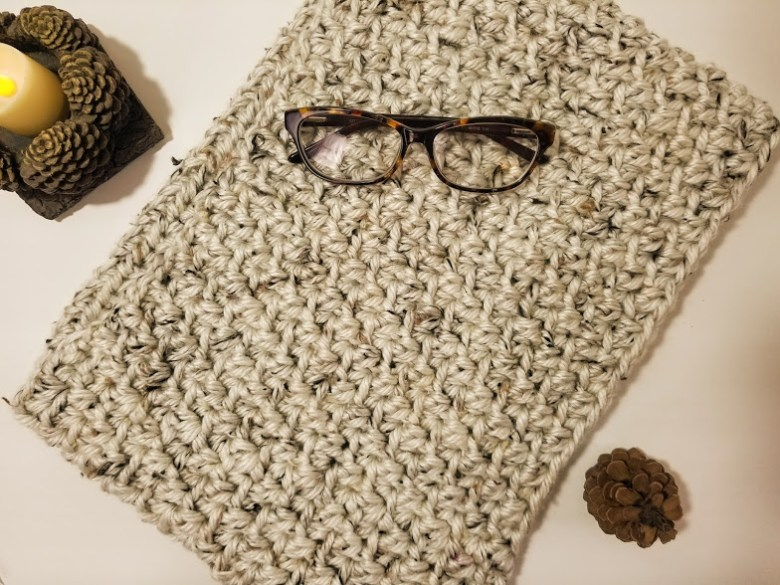 aspen tweed scarf. linen colored infinity scarf laying flat on table with a pair of glasses and some pinecones