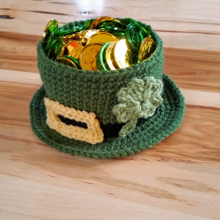 Leprechaun hat that is a bowl filled with plastic coins. Bowl has shamrock and buckle.