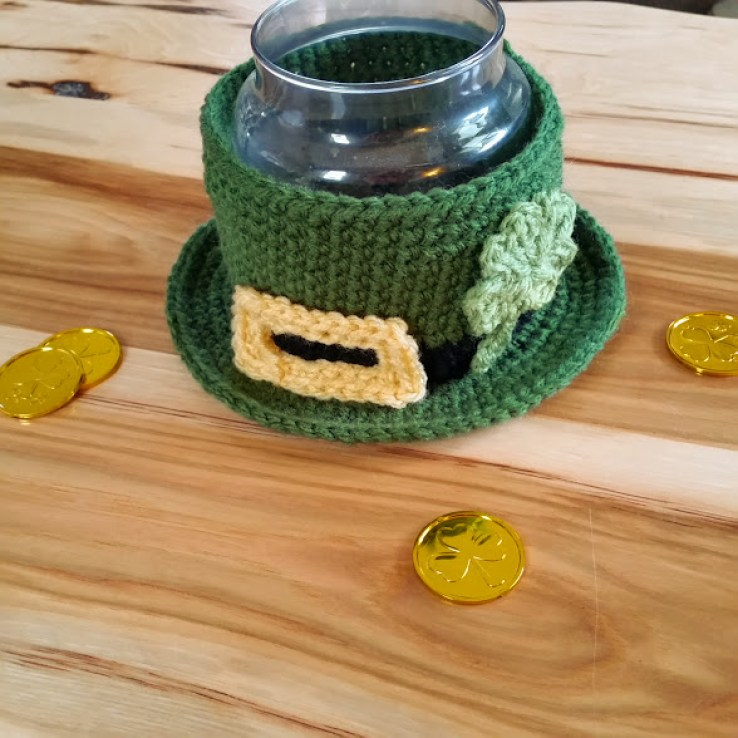 leprechaun hat bowl that has a glass candle inside. hat has buckle and shamrock appliques
