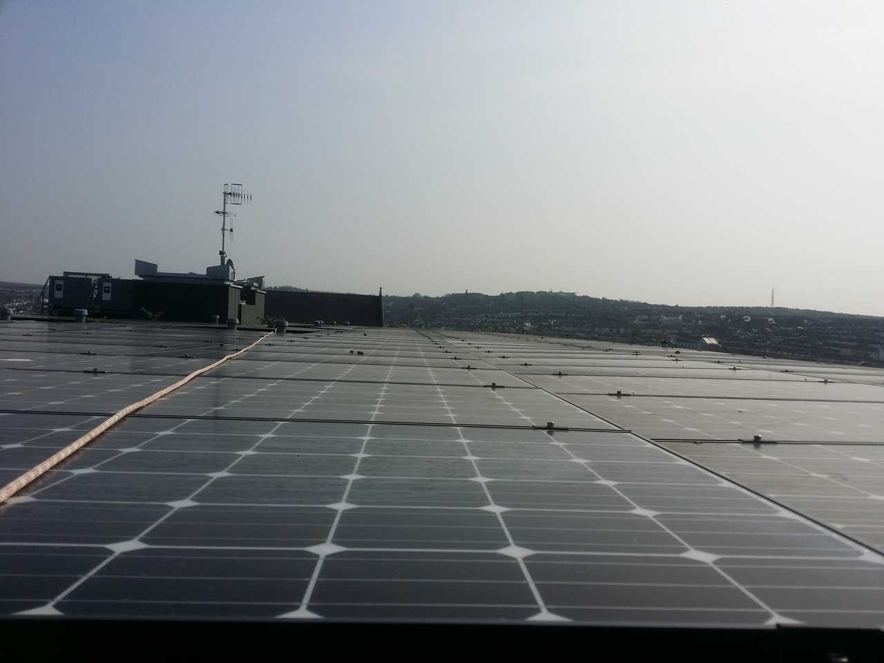 rope access teams install solar energy panels to a roof top in Brighton