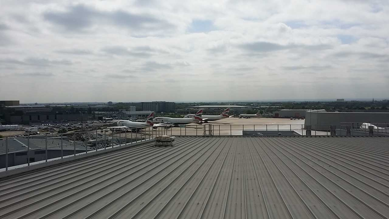 looking out over Heathrow Airport completing rope access roof cladding and glazing survey