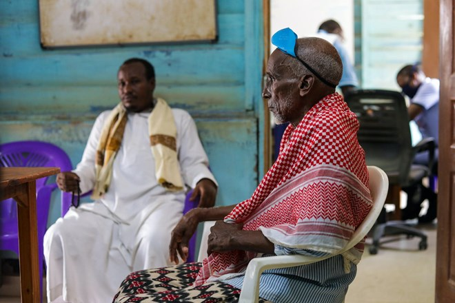 Haret Abdirahman sits with his youngest son during a consultation at MSF's mental health clinic. Haret's eldest son took his own life in August 2020./MSF