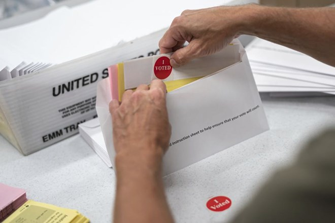 """Todd Gallagher prepares mail-in ballot envelopes including an """"I voted"""" sticker in Minneapolis in July. Absentee ballots are being requested at a record level this year. Nearly 470,000 Minnesotans have requested to vote absentee. That's 12 times the number requesting mail-in voting at this point in 2018. This year's demand obliterates the demand in the 2016 Presidential election, when only 20,000 absentee ballots were requested by July 24.GLEN STUBBE – STAR TRIBUNE"""