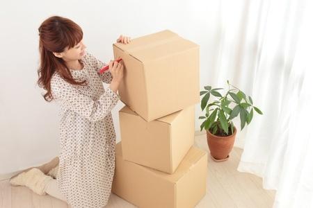 荷造り梱包したダンボールにマジックで記入している女性