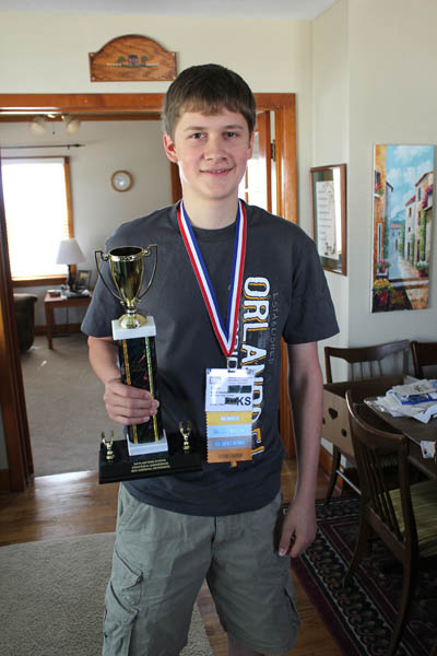 Erich Herbel holds the third-place trophy he and classmate Chase Meisinger earned in the Structural Engineering contest at the Technology Student Association?s national convention in Orlando, Fla., last week. Herbel also placed among the top 10 in Drag?ster Design and Flight Endurance, becoming the first Hills?boro High School contestant to earn three top-10 finishes. Don Ratzlaff / Free Press