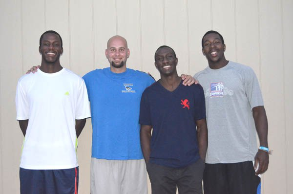 Tabor College men?s basketball coach Micah Ratzlaff (second from left) has added two athletes from Grenada to the 2013-14 Bluejay roster: a 6-foot, 8-inch center Jonathan Gibson (at left)?and 6-7 forward/center Andrew Thomas (at right). Pictured with them is former Tabor athlete and 2009 graduate, Grenada native Orson Thomas, who helped both men get to Tabor.