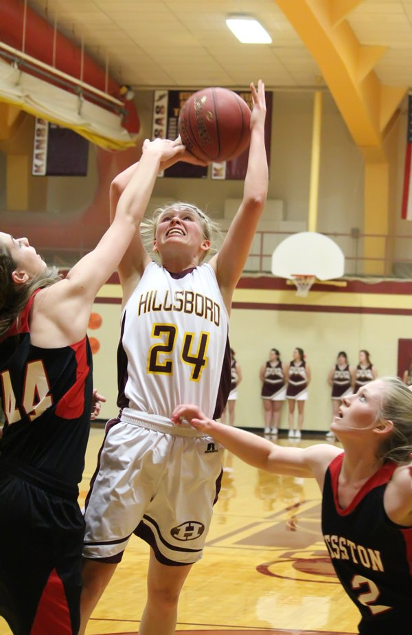 Addie Lackey (24) is fouled by Hesston's Kelsey Unruh on a drive to the basket. Lackey scored 15 points in defeat.