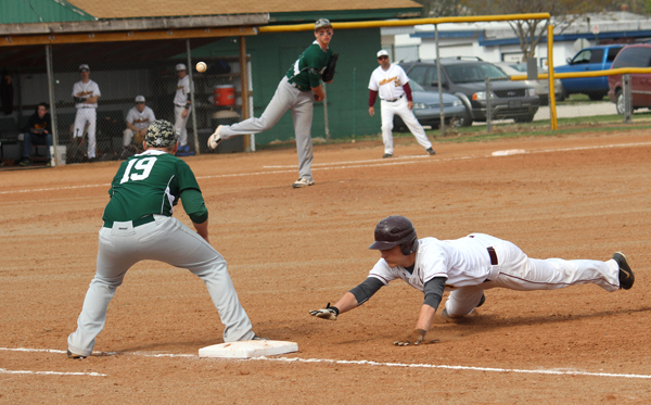Sophomore Tyson Reimer dives safely back to first base on a pick-off attempt by Pratt pitcher Sean Noel early in Game 1. Don Ratzlaff / Free Press
