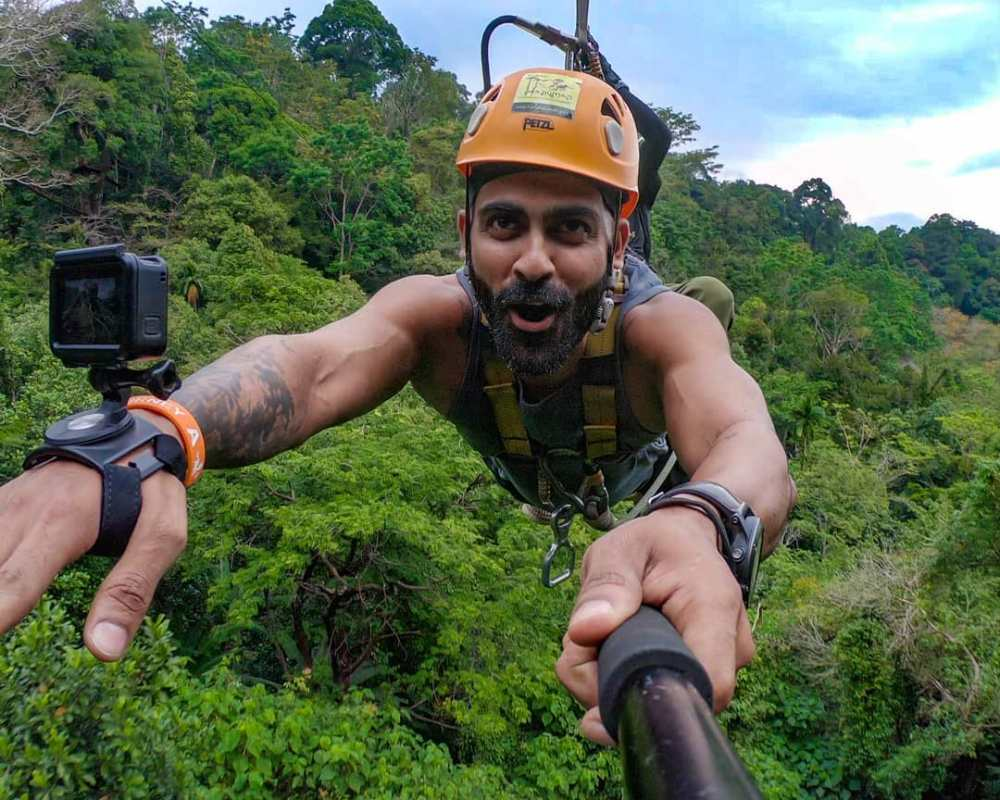Delton Dsouza on zipline over some forest with Action cameras mounted on his body.