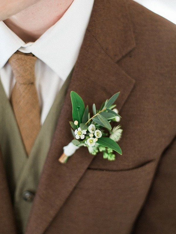 White and green boutonniere on brown and green suit