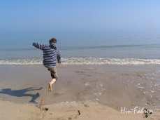Junge springt mit Freude ins Meer am Utah Beach