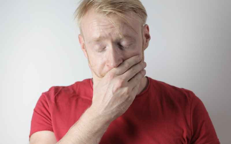 stressed male worker covering mouth with hand against gray background