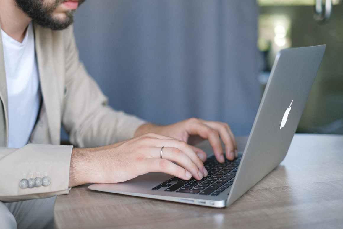 crop bearded businessman browsing portable laptop indoors