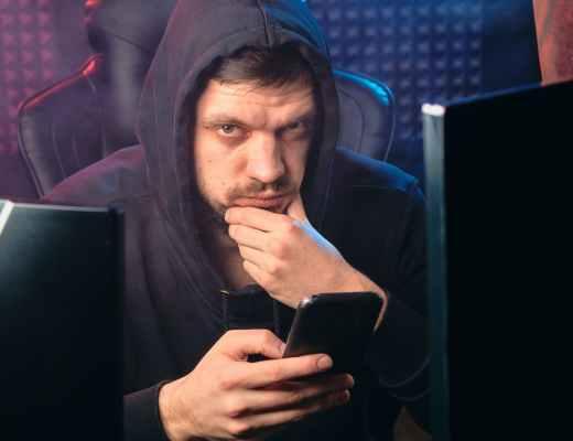 man in black hoodie holding black smartphone