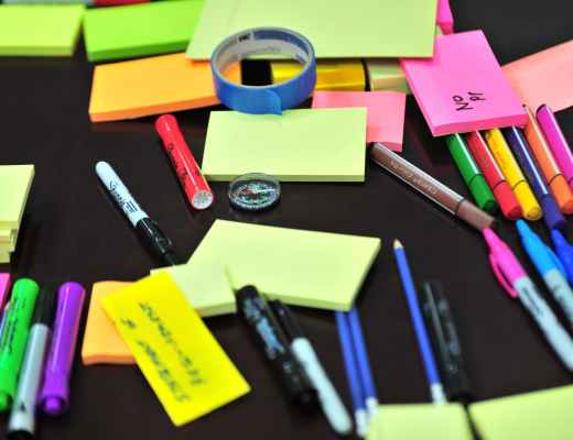 photo of sticky notes and colored pens scrambled on table