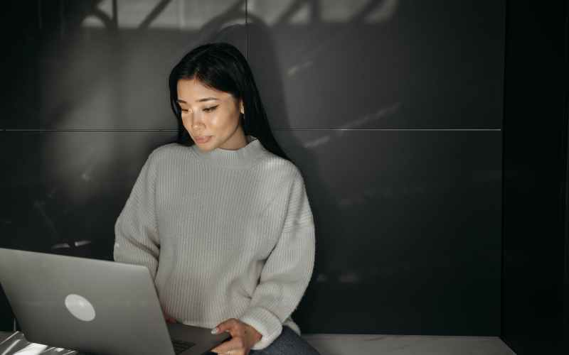 woman in white sweater using laptop