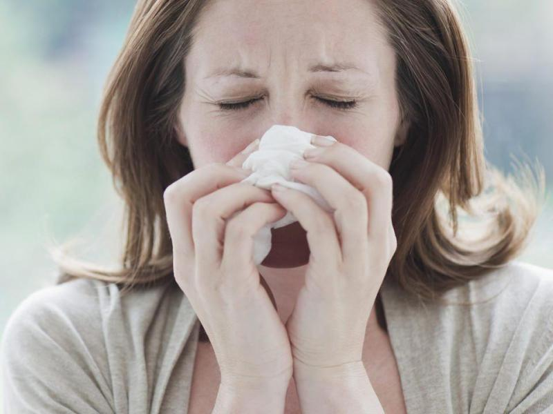 Sick woman wiping her nose