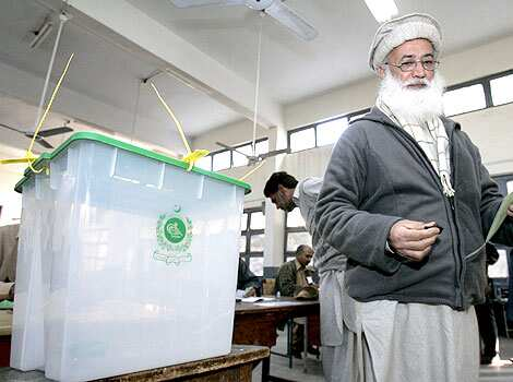 A Pakistani man walk next to ballot box after he collected his voting paper at a polling station in Islamabad. Pakistan votes