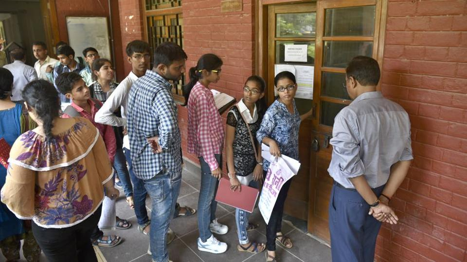 Students wait in queue for submitting their documents for the new academic year 2017-18 at Hans Raj College in North Campus in New Delhi, on June 27, 2017.