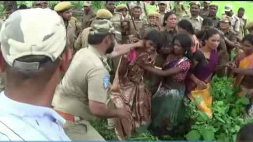 A policeman attached to the Telangana forest department restrains a tribal woman in Jalagalancha.