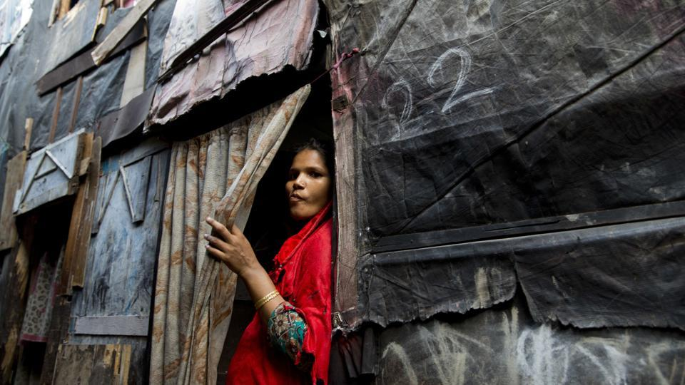 A Rohingya Muslim woman stands by the entrance to her shanty at a camp for refugees in New Delhi on September 18, 2017.