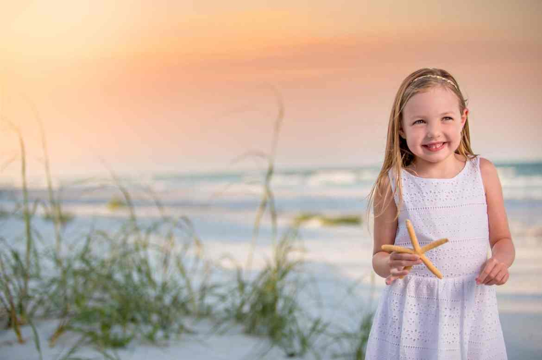 New Smyrna beach photographer captures a portrait of a child on new Smyrna beach at sunset holding a starfish