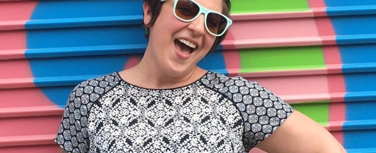 rae pagliarulo in sunglasses against colorful wall