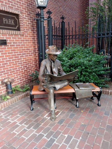 bronze statue of man reading newspaper on a bench in a lancaster brick alcove