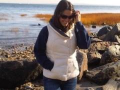 rachel-blumenfeld by water standing on rocks wearing vest and sunglasses