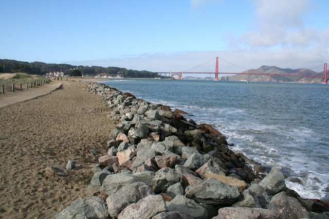 view of golden gate from crissy field with beach, path and rocks