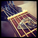 neck of guitar with pick under strings