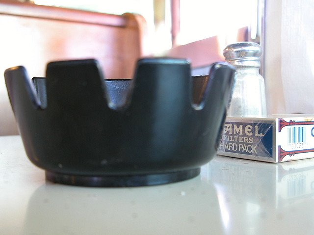 ash tray and pack of Camel cigarettes on diner table with salt and paper in background