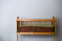 crib left of center in photo - empty, bumper with green ribbons