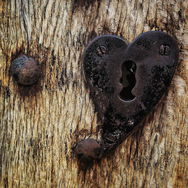 rustic wood door with rusty nail and heart-shaped lock