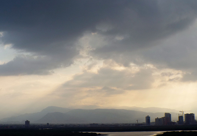 dark rain clouds and rain with a little light peeking through over city in UAE, mountains in distance