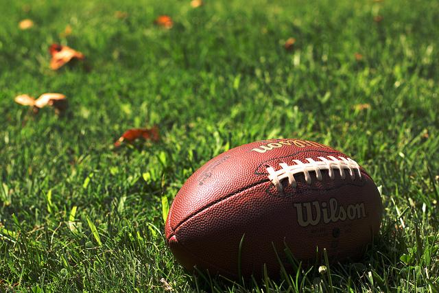 football on grassy field, a few fall leaves around