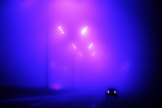 car alone on highway, taillights on, bright street lights in blue and purple