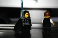 luke skywalker lego guy with blue lightsaber next to unknown lego guy