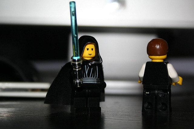 luke skywalker lego guy with blue lightsaber next to unknown lego guy