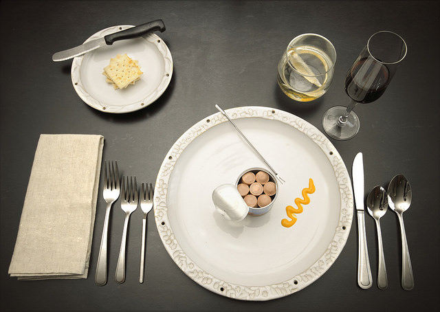 vienna sausages n can on fancy plate and formal place setting with wine - an ironic photo