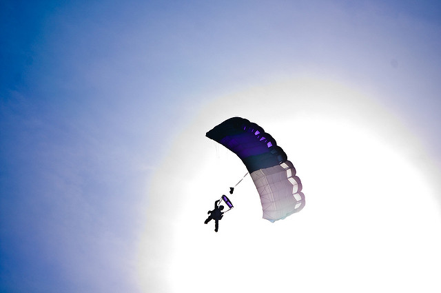 parachute in sky, center of frame with bright sunburst behind