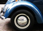 close up of blue VW wheel with reflection of building in hubcab