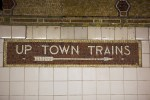 tiles on subway statopm wall and sign that says up town train with arrow pointing to the right