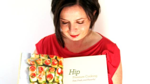 "Laura Pazzaglia, the author, holds open ""Hip Pressure Cooking: Fast, Fresh & Flavorful"" to give readers a sneak-peek at the first pages."