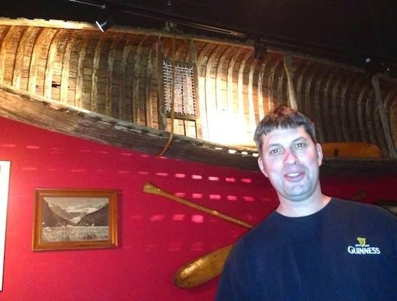 Kevin Tessier, host raconteur par excellence, below classic canoe, at Sun Peaks Voyageur Bistro