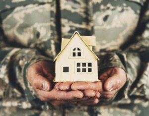 Military service member holding little cardboard house