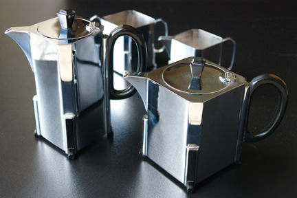 chrome Art Deco tea set with black bakelite handles & knobs comprises tea pot, hot water pot, milk jug and sugar bowl