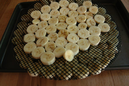 sliced bananas on two pizza cooking mesh sheets