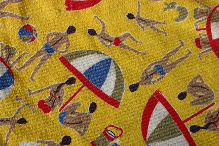 detail of vintage beach bag made of bright yellow 1950s towelling fabric with beach umbrella and male & female swim-suited figures pattern